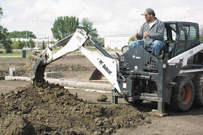 Operator uses a Bobcat backhoe attachment to dig a utility trench in a home building site.