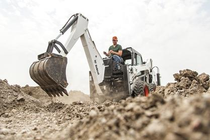 A bucket with the Bobcat backhoe attachment is used to dig into black soil.
