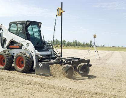 A laser box blade scraper on a Bobcat skid-steer loader.