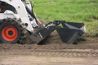 A combination bucket attachment is used to grade a dirt road with a Bobcat skid-steer loader.