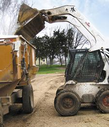 Bobcat skid-steer loader uses a bucket to dump feed into a grain trailer.