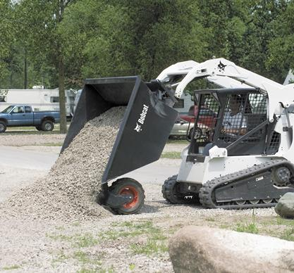 Compact track loader unloads landscaping material from the Bobcat dumping hopper attachment.