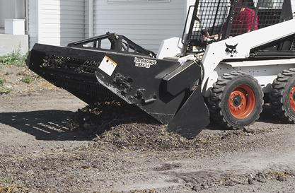 Bobcat skid-steer loader and landscape rake attachment on a lawn in a residential neighborhood.