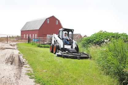 Bobcat skid-steer loader with mower attachment to mow alongside ditch with barn in background.