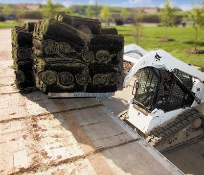 Bobcat compact track loader lifts a heavy load of sod with the pallet fork attachment.