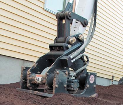 Dirt along the foundation of a house is compacted with the Bobcat plate compactor attachment.