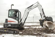 Bobcat E35i compact (mini) excavator with a pro clamp attachment moving a concrete pipe.