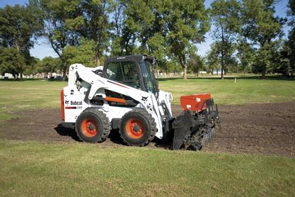 Seeder attachment mounted on a Bobcat S650 skid-steer loader plants grass.