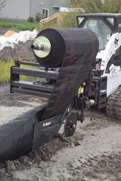 Silt fence is placed in an erosion zone using the silt fence installer attachment on a Bobcat compact track loader.
