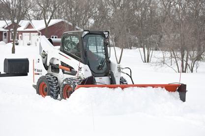 Bobcat snow blade (snowblade) attachment is used to remove snow from a driveway.