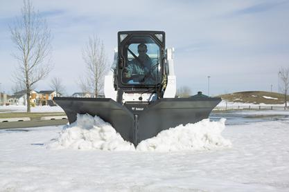 Snow V-blade attachment mounted on a Bobcat skid-steer loader plows snow from a parking lot.