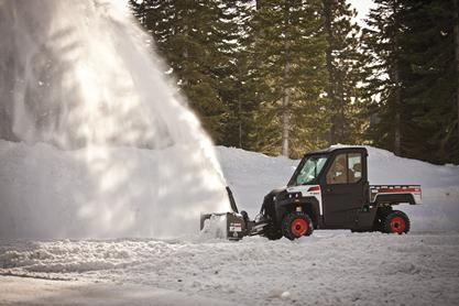 Powerful Bobcat UTV snowblower attachment blows snow away from a parking area.