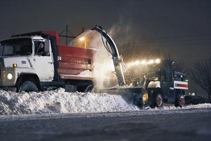 Toolcat utility work machine with snowblower and spreader blowing snow into dump truck in a parking lot.