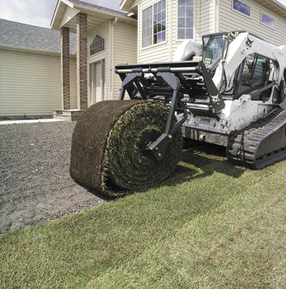 Sod layer attachment mounted to a Bobcat compact track loader lays a lawn for a newly constructed house.