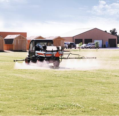 Bobcat sprayer attachment in the box of a 5600 Toolcat is used to spray fertilizer on a lawn.