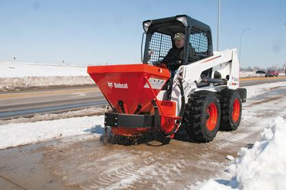 Spreader attachment mounted on a Bobcat skid-steer loader lays sand on a sidewalk.