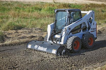 Bobcat tiller attachment prepares black dirt for seeding.