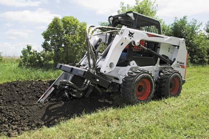 Trencher attachment mounted to a Bobcat skid-steer loader digs a long trench in the yard of a country home.
