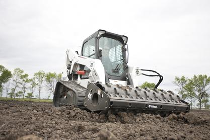 Bobcat vibratory roller attachment packs dirt in an open area.