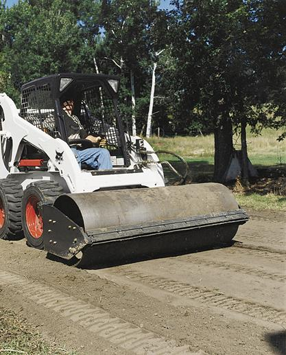 Vibratory roller attachment on a Bobcat skid-steer roller packs black dirt for a roadway.