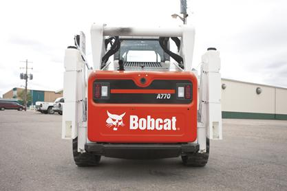 Water kit tanks mounted on the uprights of a Bobcat all-wheel skid-steer loader.
