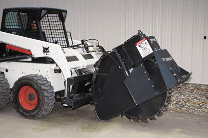 Wheel saw attachment mounted on a Bobcat skid-steer loader.