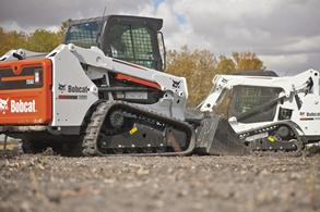 Pair of Bobcat compact track loaders moving on jobsite.