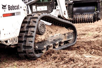Bobcat T550 compact track loader drives through sandy soil.