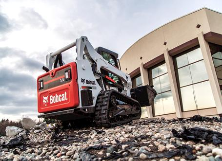 Bobcat T595 lifting material at a commercial construction site with a bucket.
