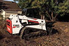 Bobcat T630 compact track loader uses a bucket to move dirt on a construction jobsite.