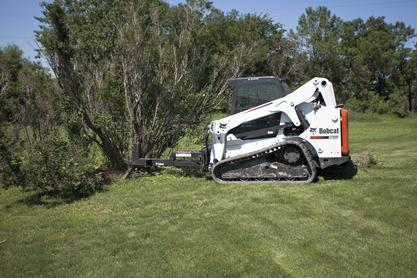 Bobcat brush saw (cutter) attachment is used to remove a tree in a wooded area.