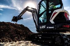 Bobcat E35 compact (mini) excavator and bucket attachment digging into a dirt pile.