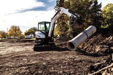 Bobcat E35 R-Series compact excavator moving a concrete culvert.
