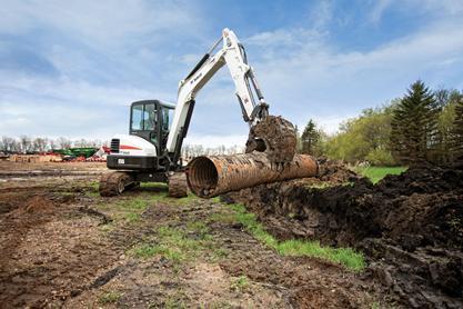 Bobcat compact excavator (mini excavator) places pipe.