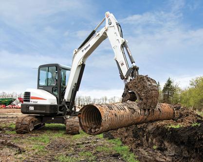 Bobcat E55 compact excavator (mini excavator) lifts drain pipe.