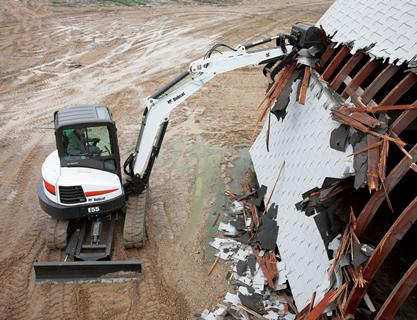 Bobcat E55 compact excavator demolishes building.