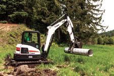 Bobcat E55 compact (mini) track loader and grapple attachment moving a metal culvert.