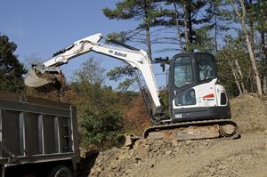 Bobcat compact excavator (mini excavator) loads truck.