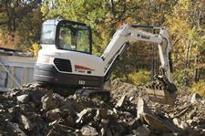 Bobcat E63 compact excavator lifting with a clamp attachment.