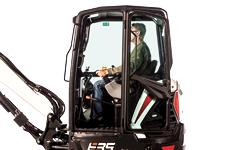 Bobcat E35 compact (mini) excavator cab with person adjusting the control console lever.