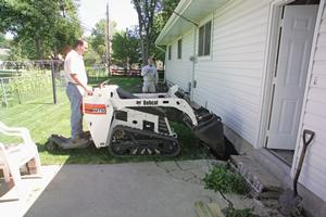 Bobcat mini track loader with bucket works along home.