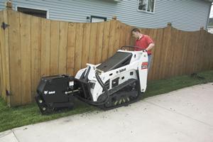 Bobcat mini track loader with vibratory plow attachment.