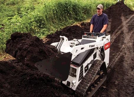 Bobcat MT85 mini track loader lifts bucket of dirt