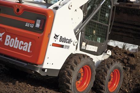 Bobcat S510 skid-steer loader moves dirt with a bucket.