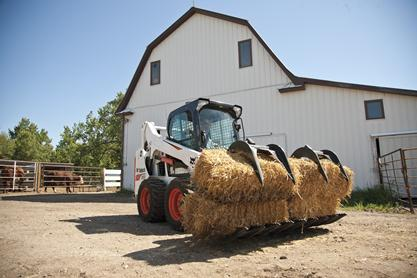 Bobcat S590 skid-steer loader with grapple attachment carrying bales of hay.