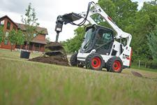Bobcat S590 skid-steer loader planting a tree with an auger attachment.