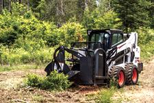 Bobcat S595 skid-steer loader uses a stump grinder attachment to remove a stump.