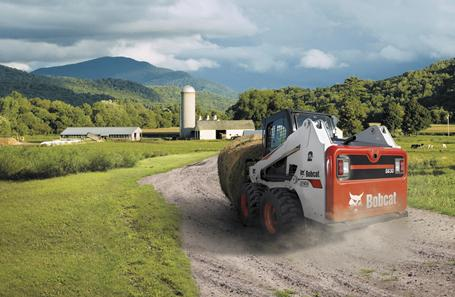 Bobcat S630 M2-Series skid-steer loader transporting a bale of hay on a farm.