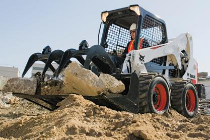 Bobcat S650 skid-steer loader with grapple attachment picks up chunks of concrete on a construction jobsite.