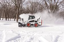Bobcat S740 skid-steer loader blows snow in the winter with a snowblower attachment.